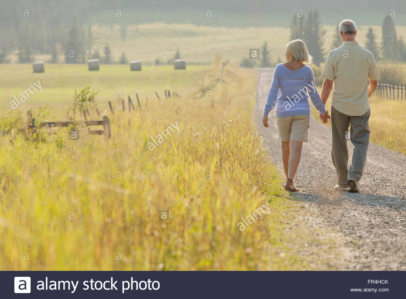 view from behind of middle-aged couple walking down country road - Stock Image