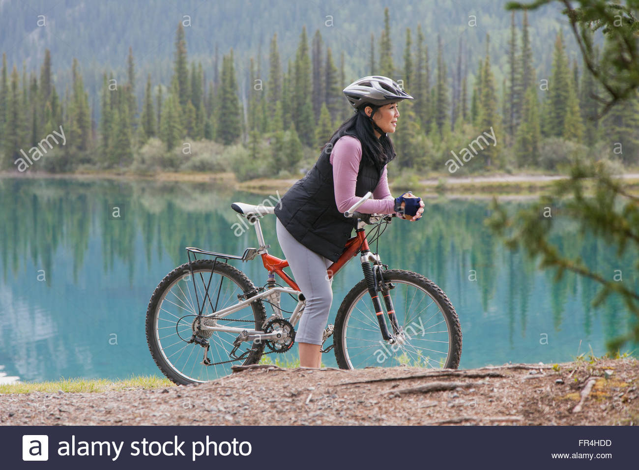 asian woman taking a pause from mountain biking by lake - Stock Image