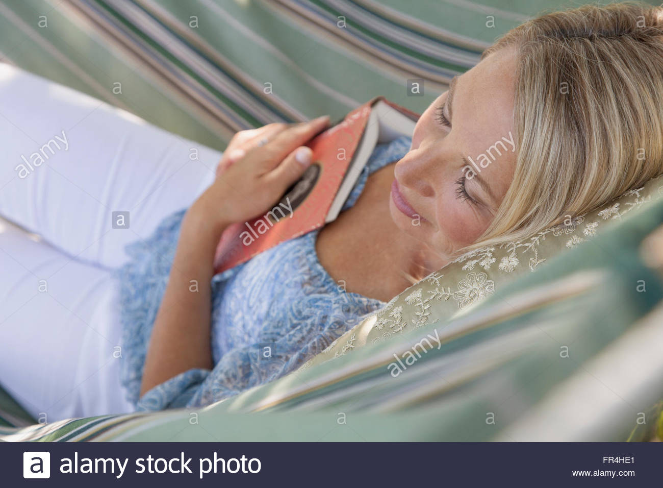 middle-aged woman napping with book in hammock - Stock Image