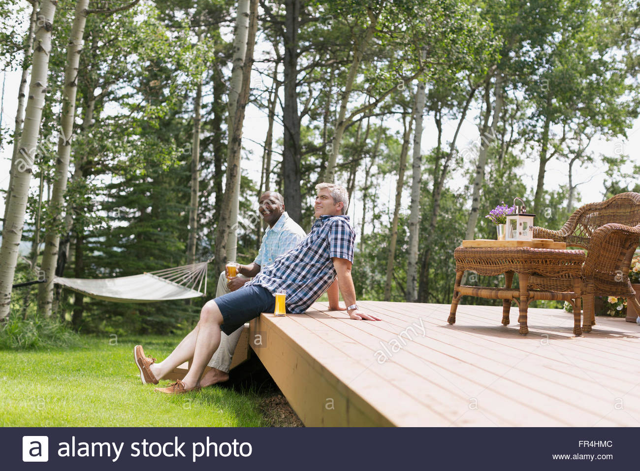 men enjoying beverages on an outdoor deck - Stock Image