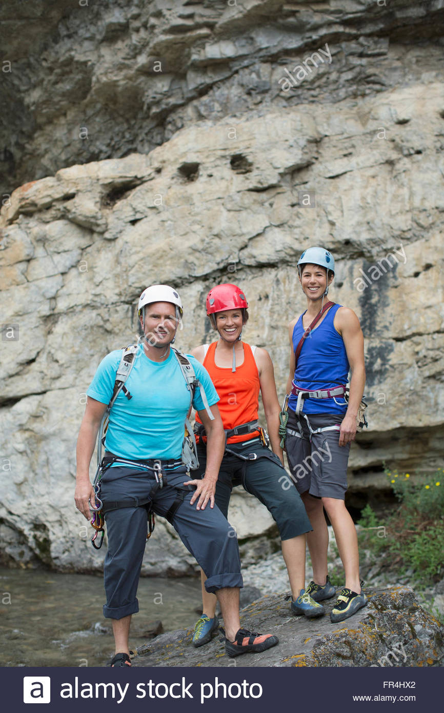portrait of three rock climbers standing in front of rock face - Stock Image