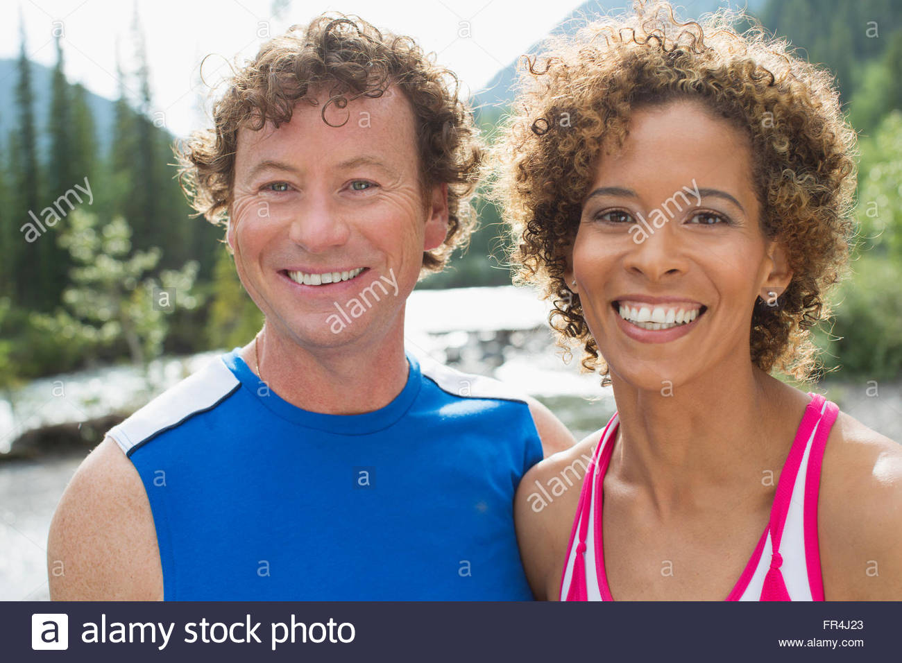 portrait of attractive, athletic couple in the woods - Stock Image