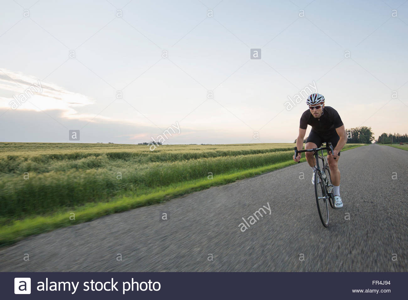 long distance bicyclist riding on highway - Stock Image