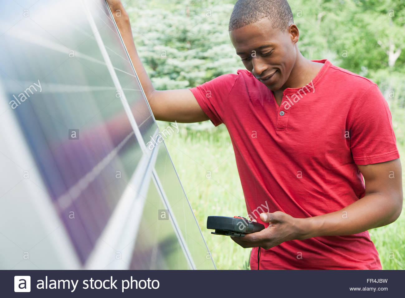 mid-adult man checking solar panel with volt meter - Stock Image