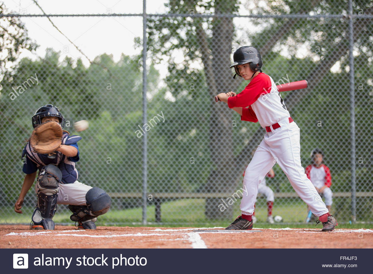 Young ball player watching pitch go past the plate. - Stock Image