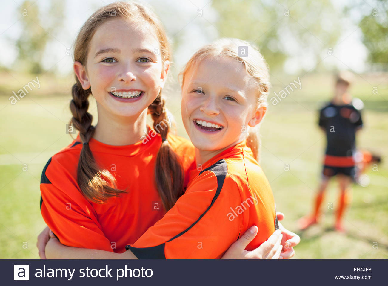 Girl soccer players smiling and hugging. - Stock Image