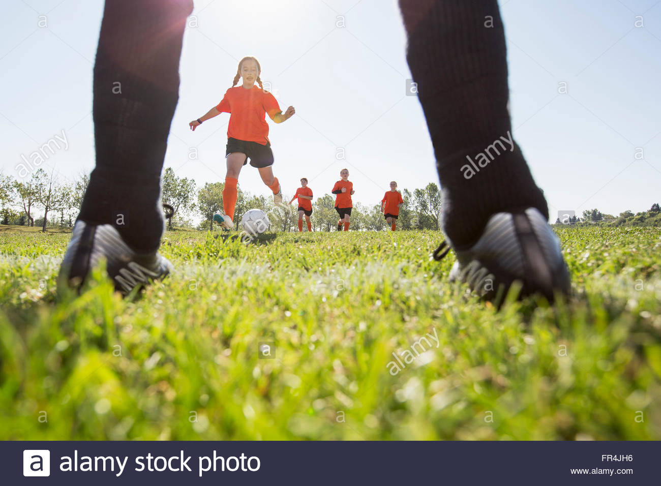young female soccer players running towards net - Stock Image