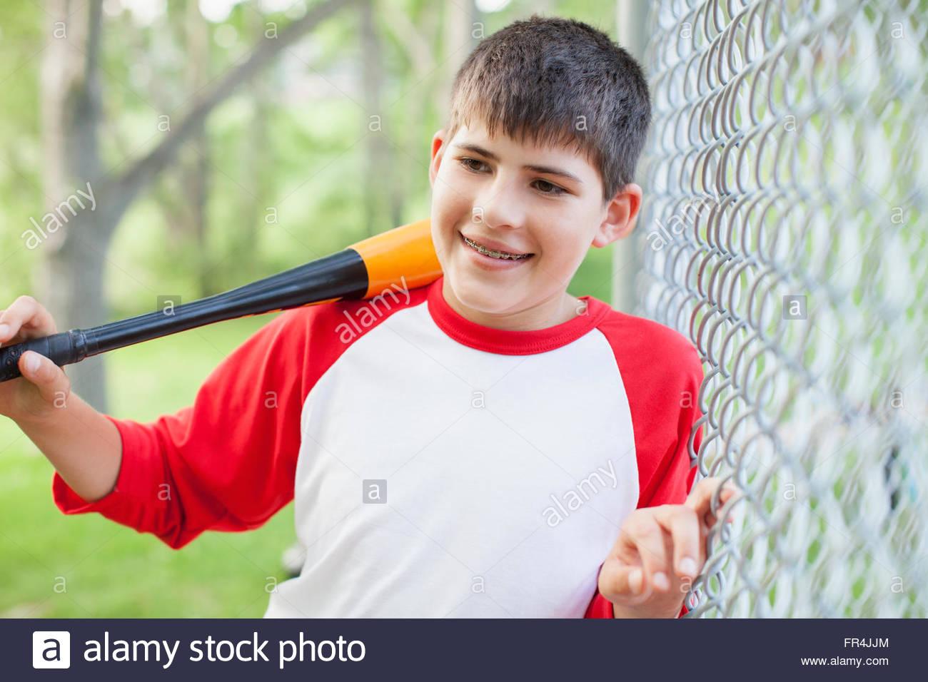 Young male baseball player with baseball bat. - Stock Image
