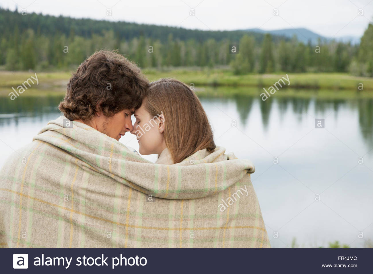Young Couple Cuddling With Blanket Along Waterfront