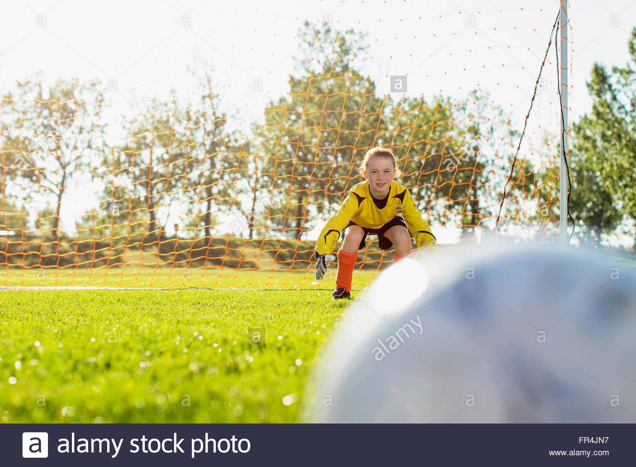 young female goalkeeper defending soccer net - Stock Image