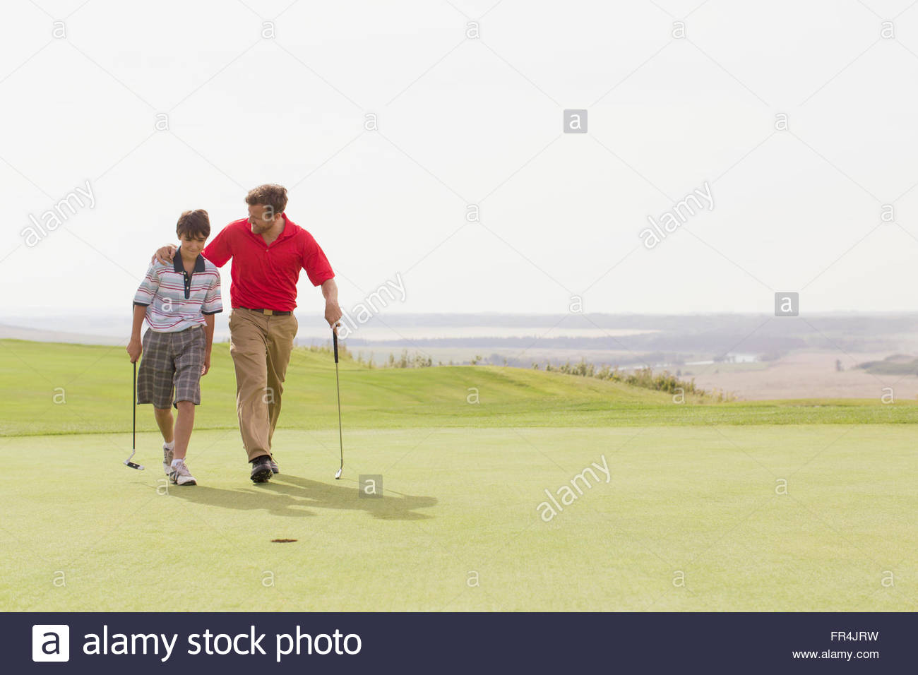 father and pre-teen son walking together on golf green - Stock Image