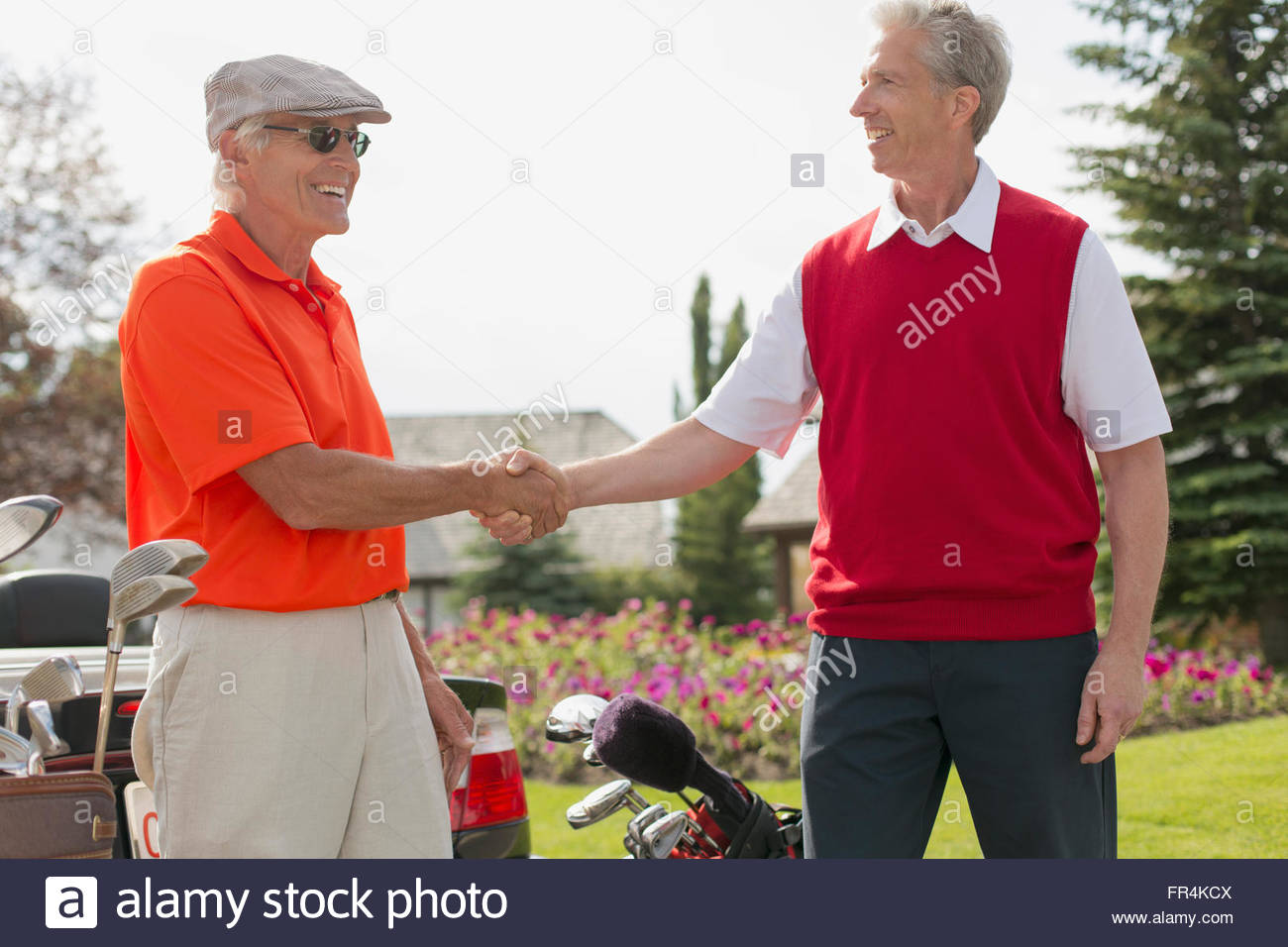 senior man and middle-aged man shaking hands after golf - Stock Image
