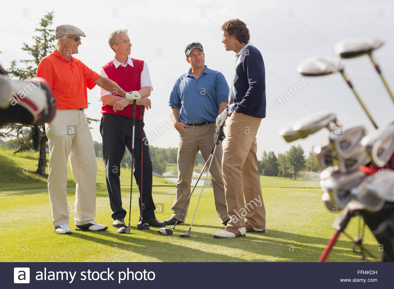 golfing foursome having a conversation on golf green - Stock Image