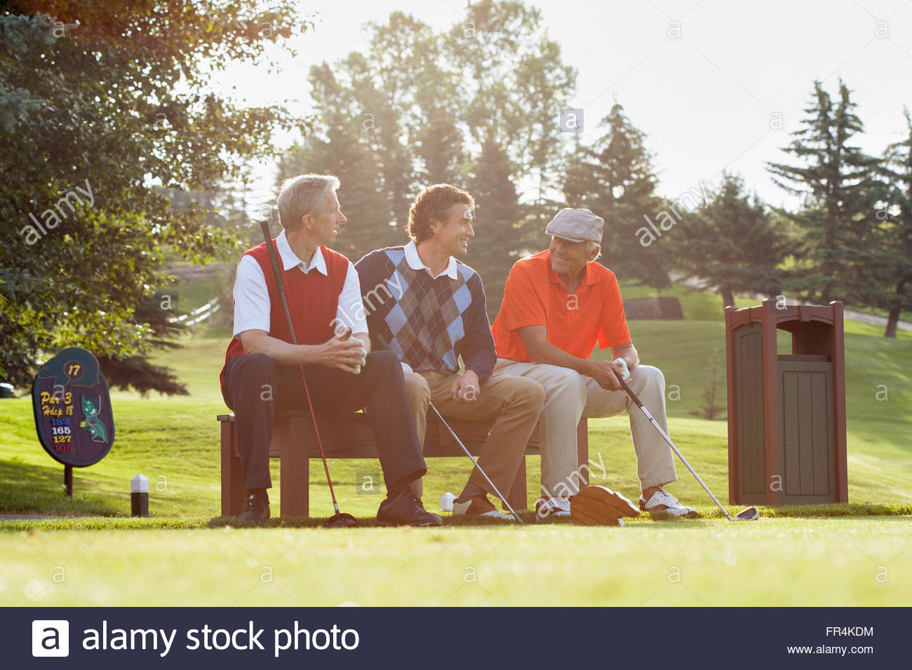 three golfers sitting on bench by tee boxStock Photo