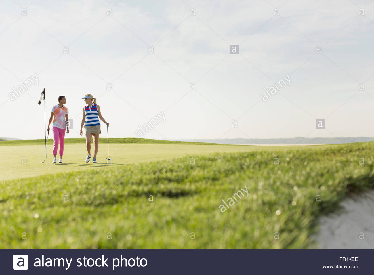two female golfers walking off golf green together - Stock Image