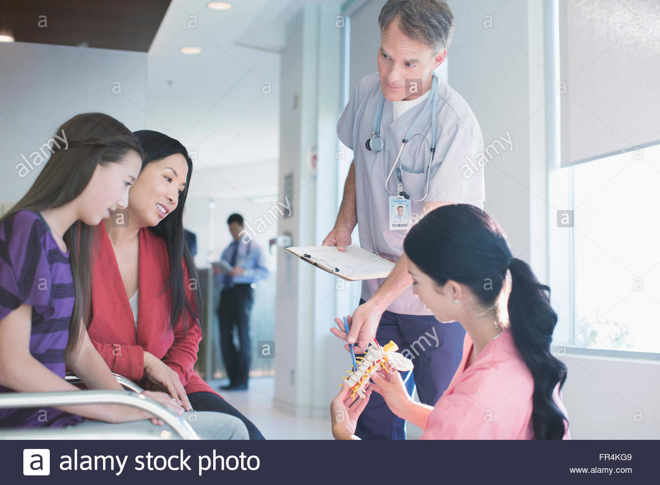 medical technician showing spinal column model to mother and daugter - Stock Image