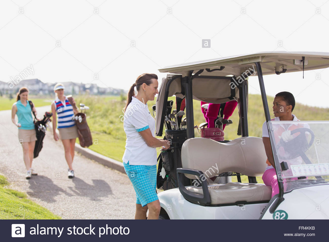 foursome of female golfers with golf cart - Stock Image