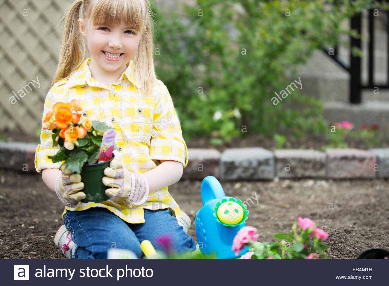 cute, 5 year old girl planting flowers - Stock Image