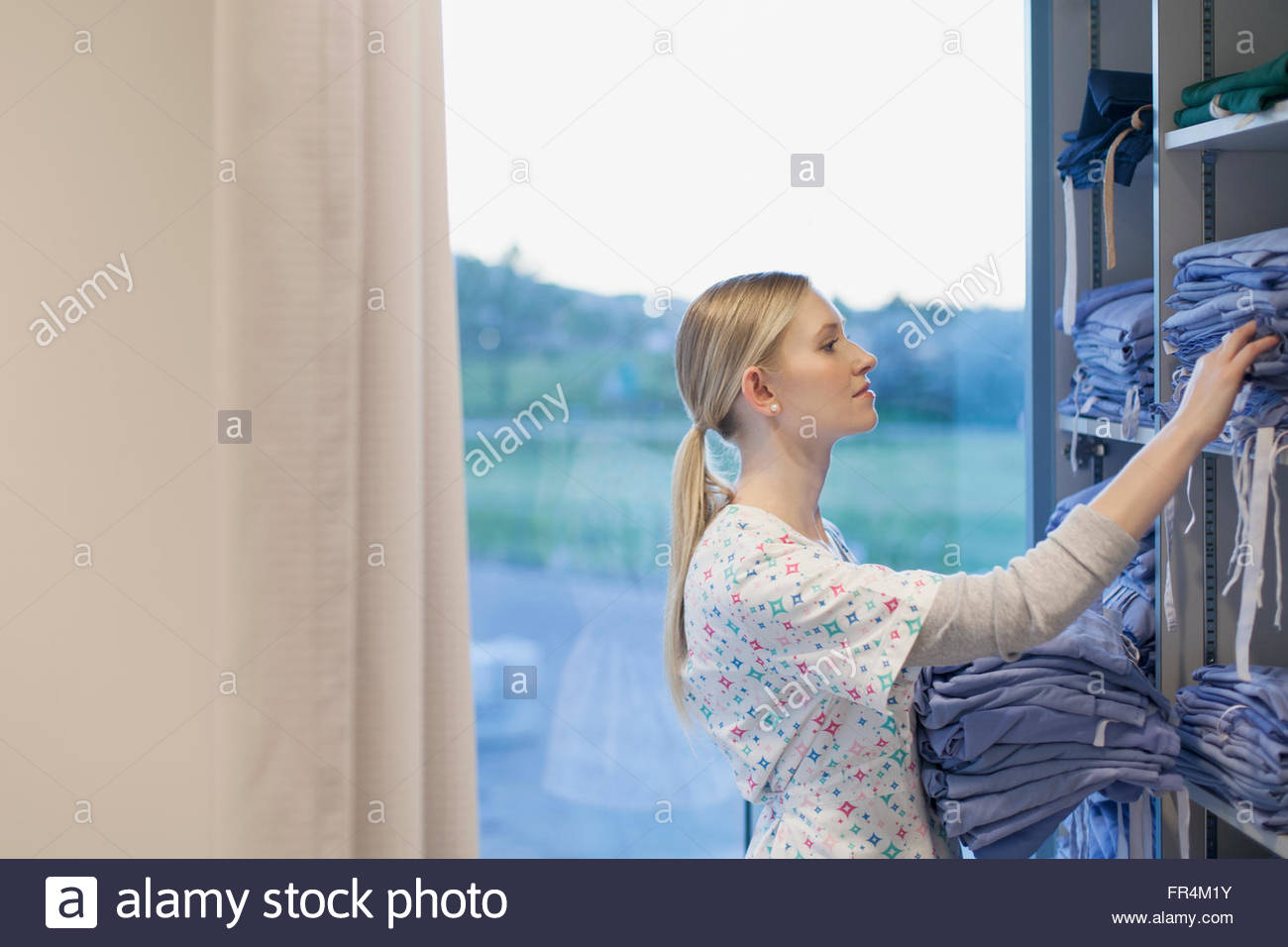 nurse checking hospital gown supplies - Stock Image