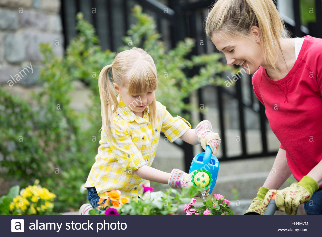 mom and 5 year old daughter maintaining flower bed - Stock Image