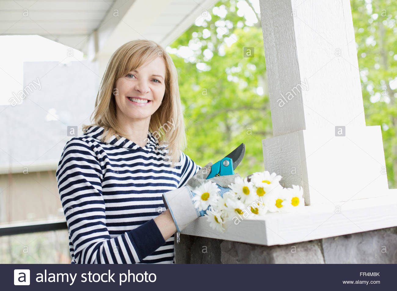 mature woman with cut flowers outdoors - Stock Image