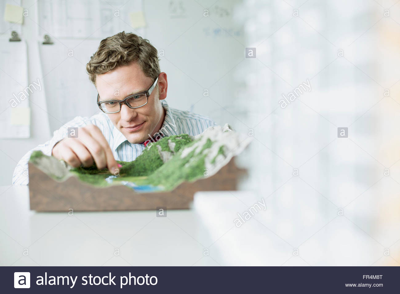 mid-adult architect working on topographical model - Stock Image
