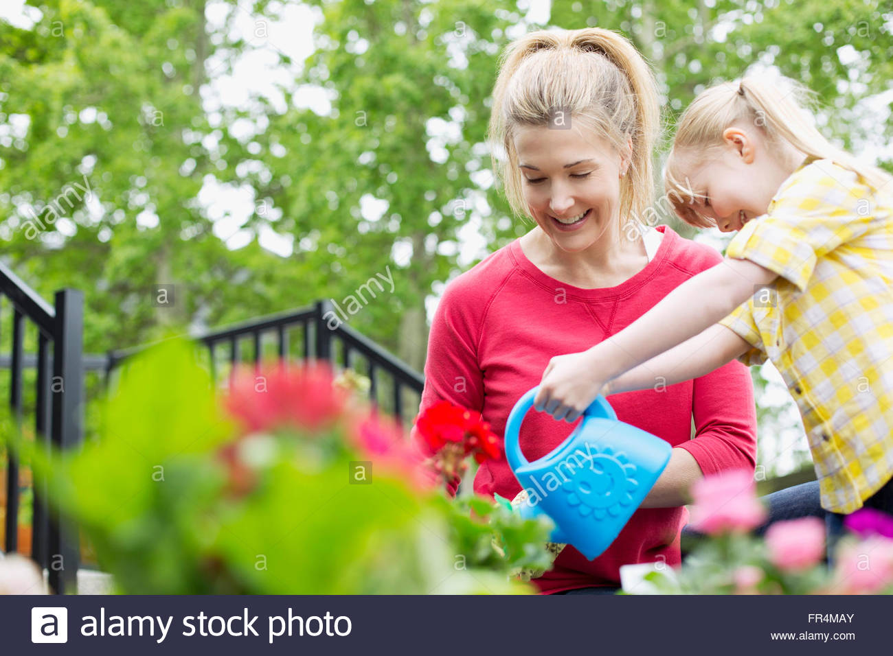 mom and 5 year old daughter watering flowers - Stock Image
