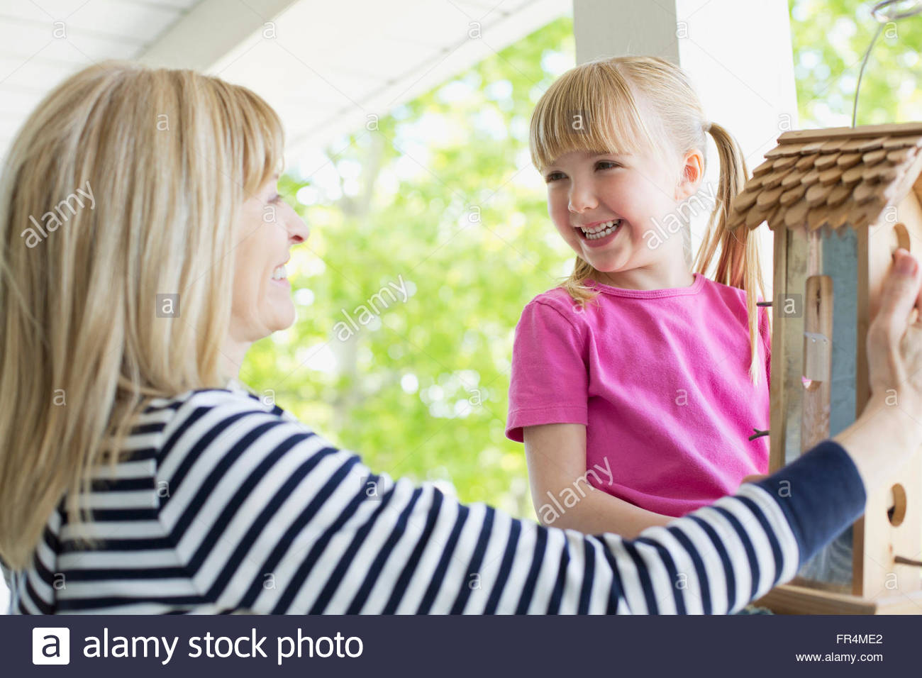 mature womam hanging a bird feeder with her grandaughter - Stock Image