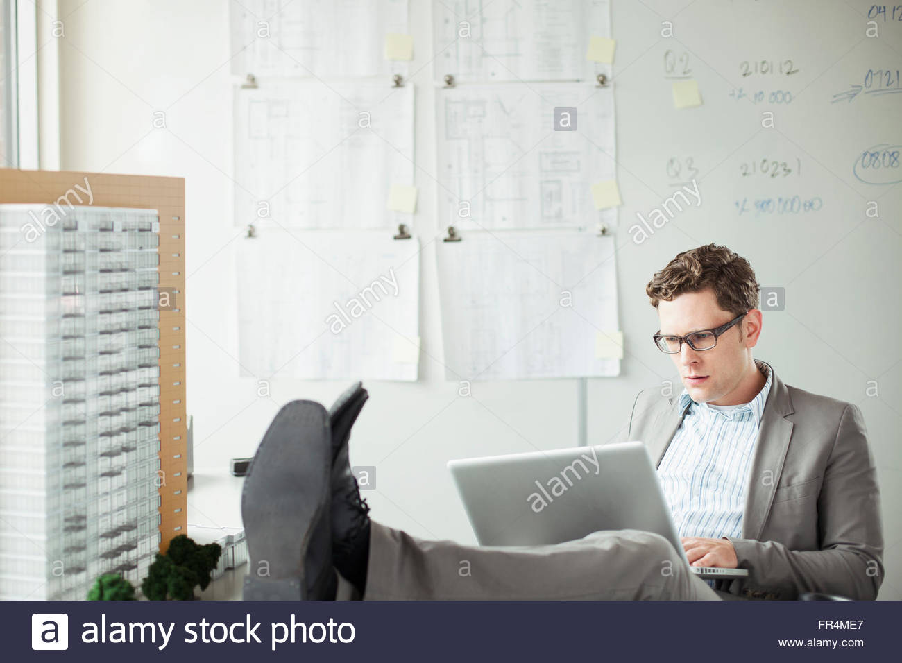 young architect with concerned look while browsing on laptop - Stock Image