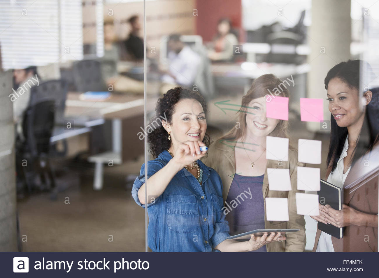 three female office workers reviewing workflow on glass wall - Stock Image