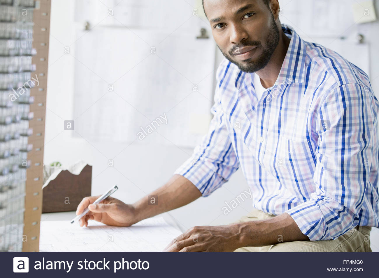 mid-adult african american archictect at desk - Stock Image