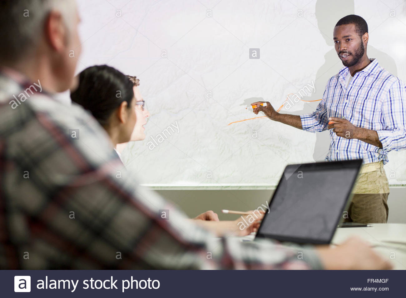 colleague presenting on whiteboard to coworkers - Stock Image