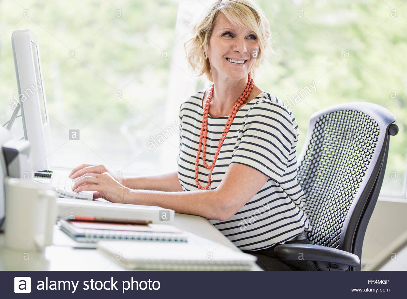 middle-aged businesswoman sitting at desktop computer - Stock Image