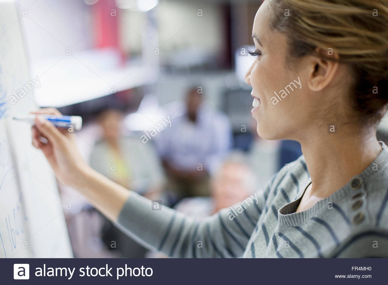 closeup of mid-adult woman writing on whiteboard - Stock Image