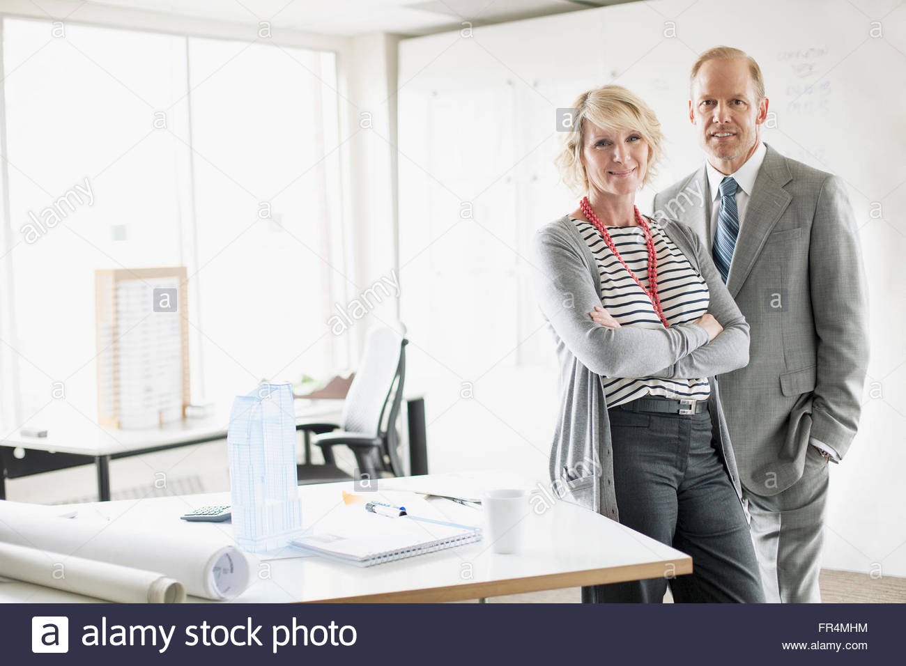 colleagues standing by desk in architect office - Stock Image