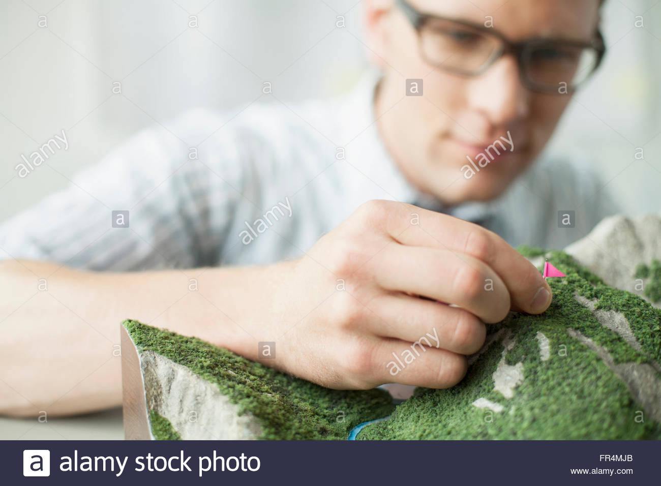 young architect putting flags on topographical model - Stock Image
