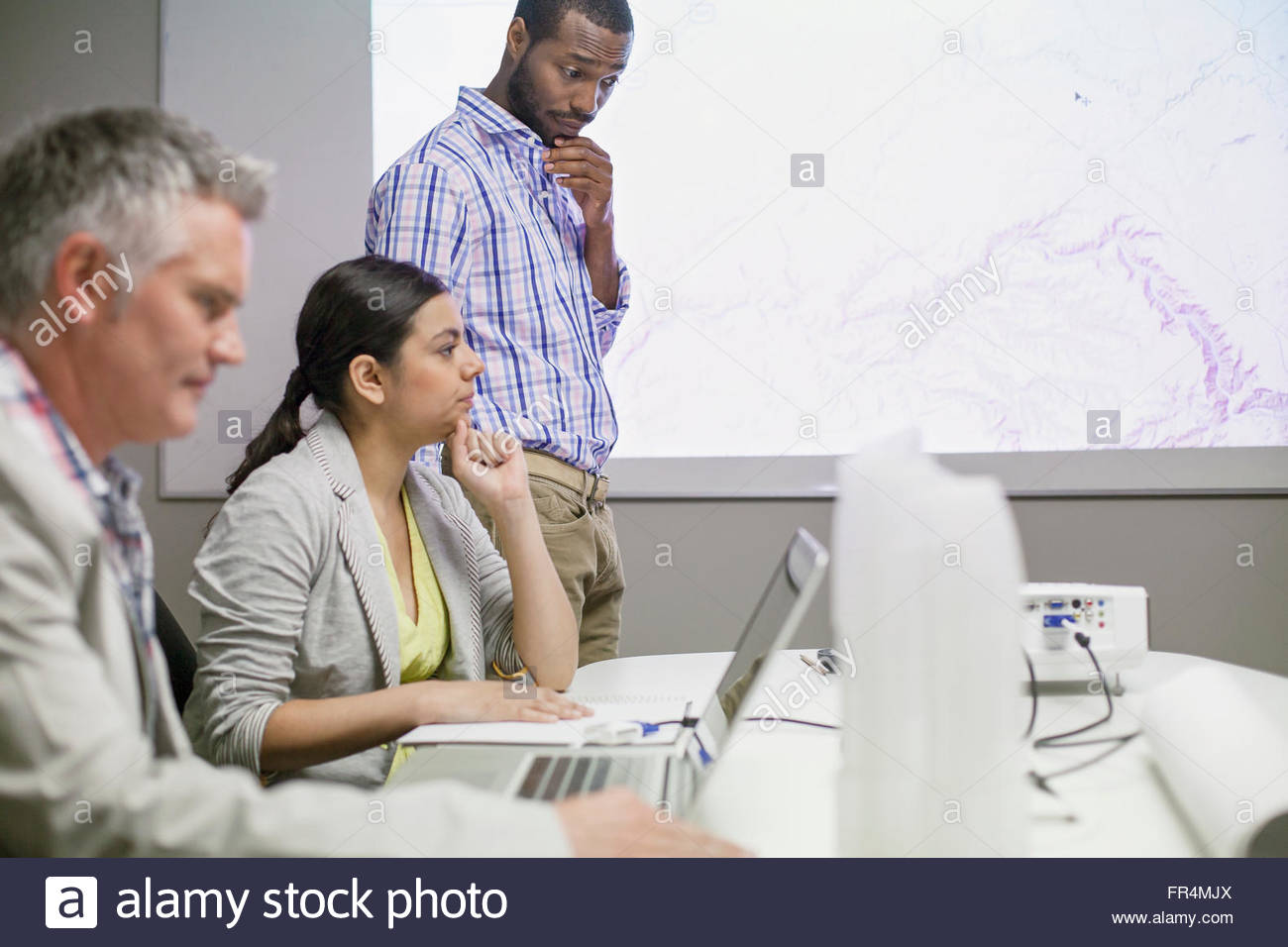 colleagues reviewing presentation together - Stock Image
