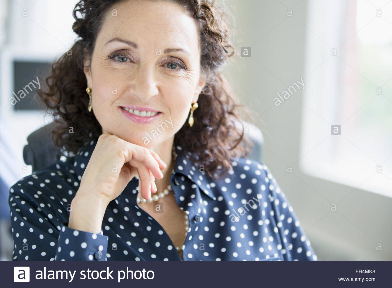 portrait of pretty, middle-aged woman at office - Stock Image
