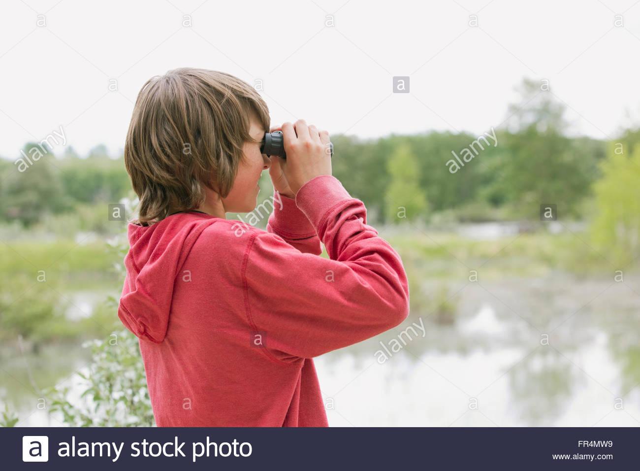 middle school student using binoculars on school trip - Stock Image