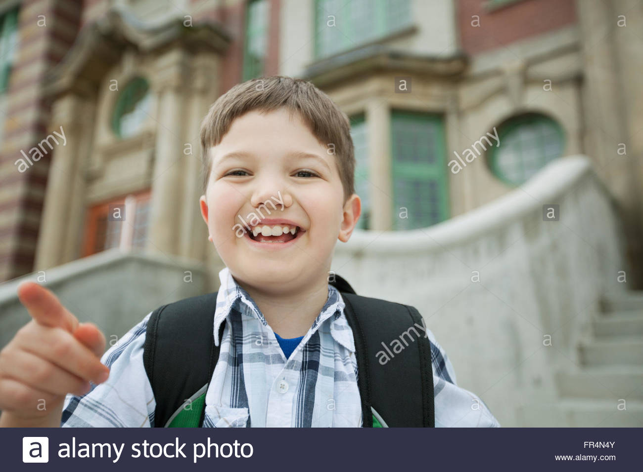 Male, elementary student standing outside school. - Stock Image