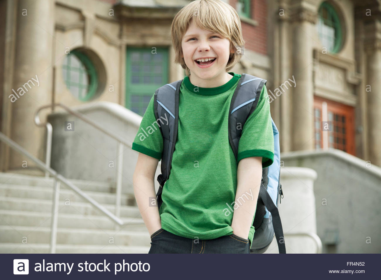 Male, elementary student in front of school building. - Stock Image