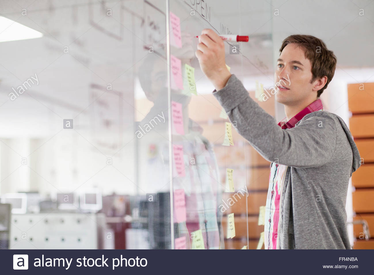 analyst drawing out strategy on glass wall - Stock Image