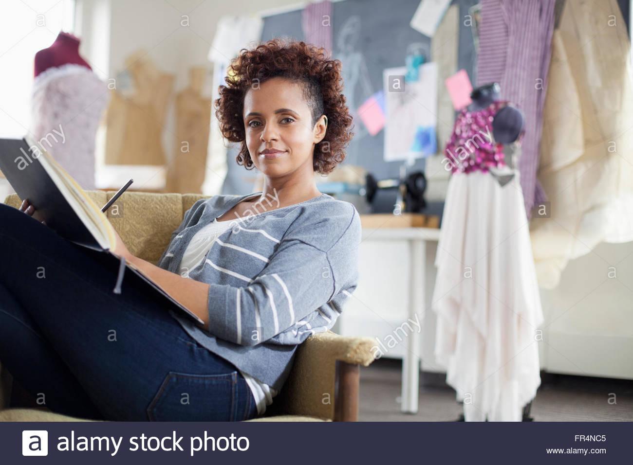 portrait of fashion designer reviewing sketchbook in studio - Stock Image