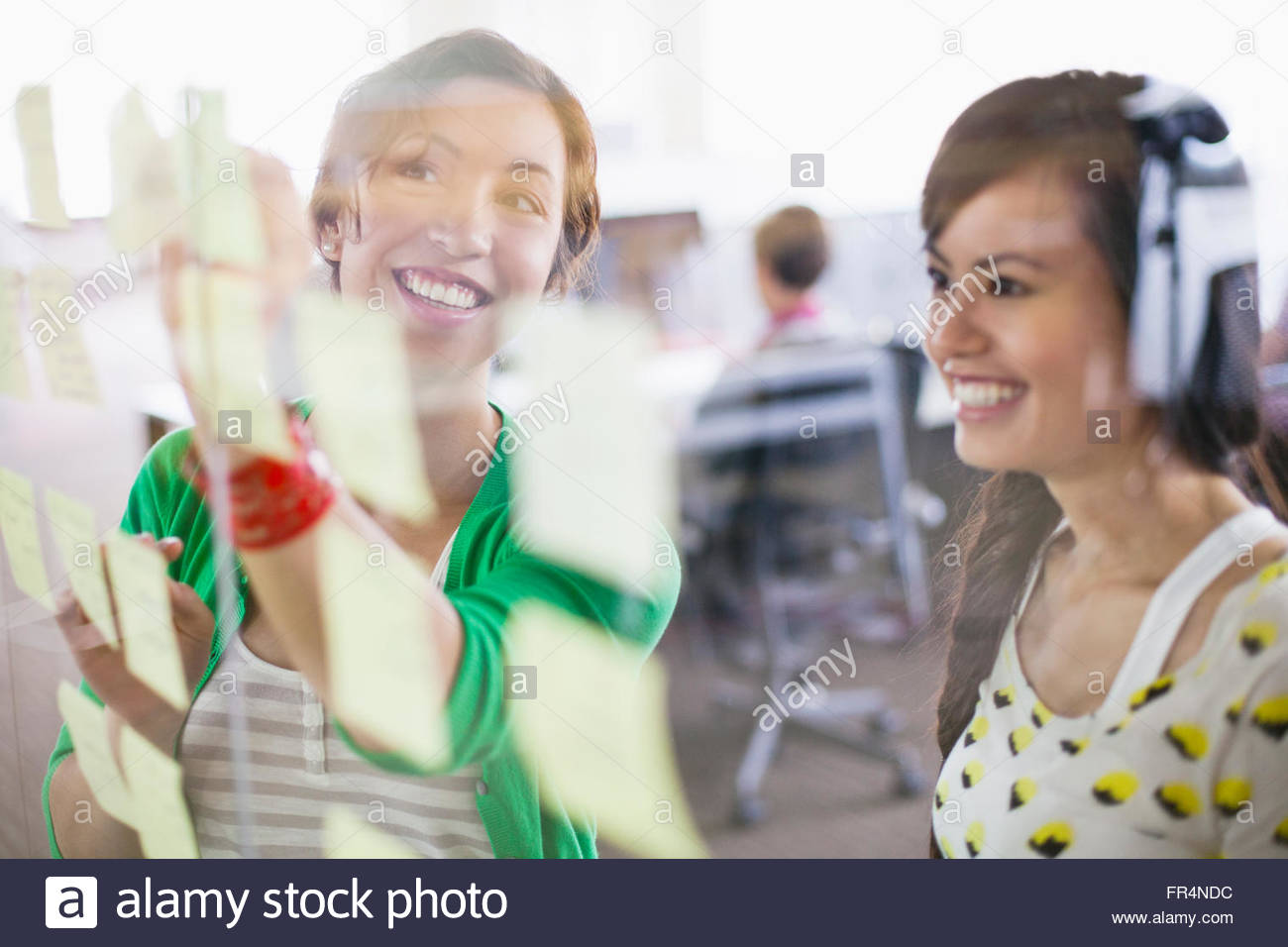 young businesswoman reviewing flow chart on glass wall - Stock Image