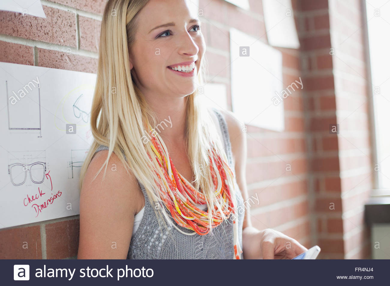 pretty, young adult designer with smartphone - Stock Image
