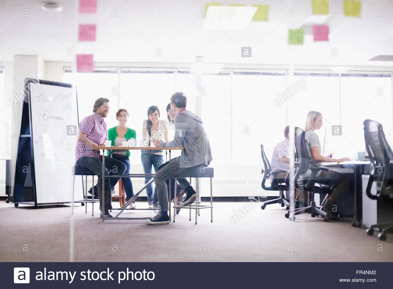 coworkers working in trendy business office - Stock Image