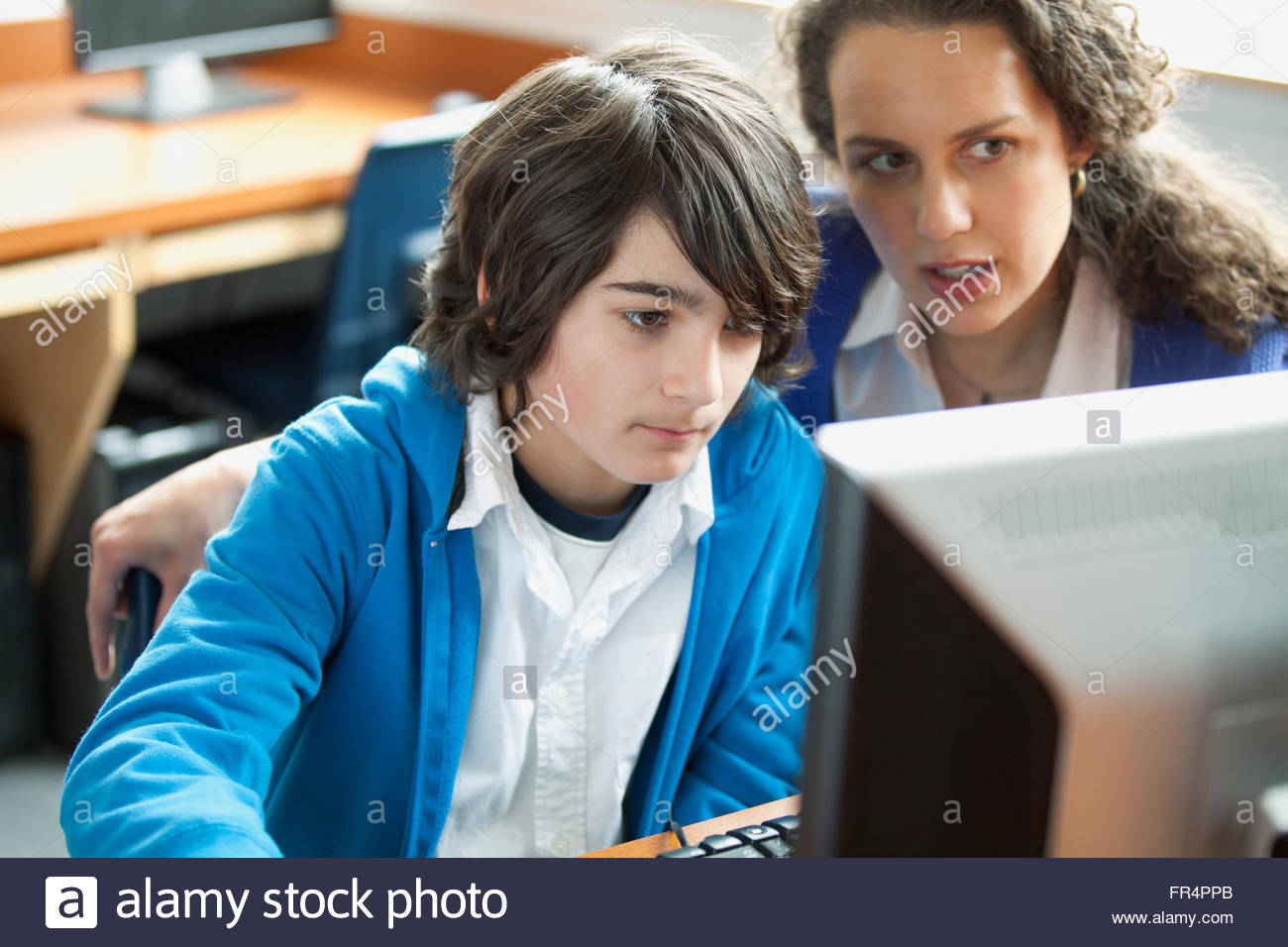 teacher assisting middle school student on computer - Stock Image