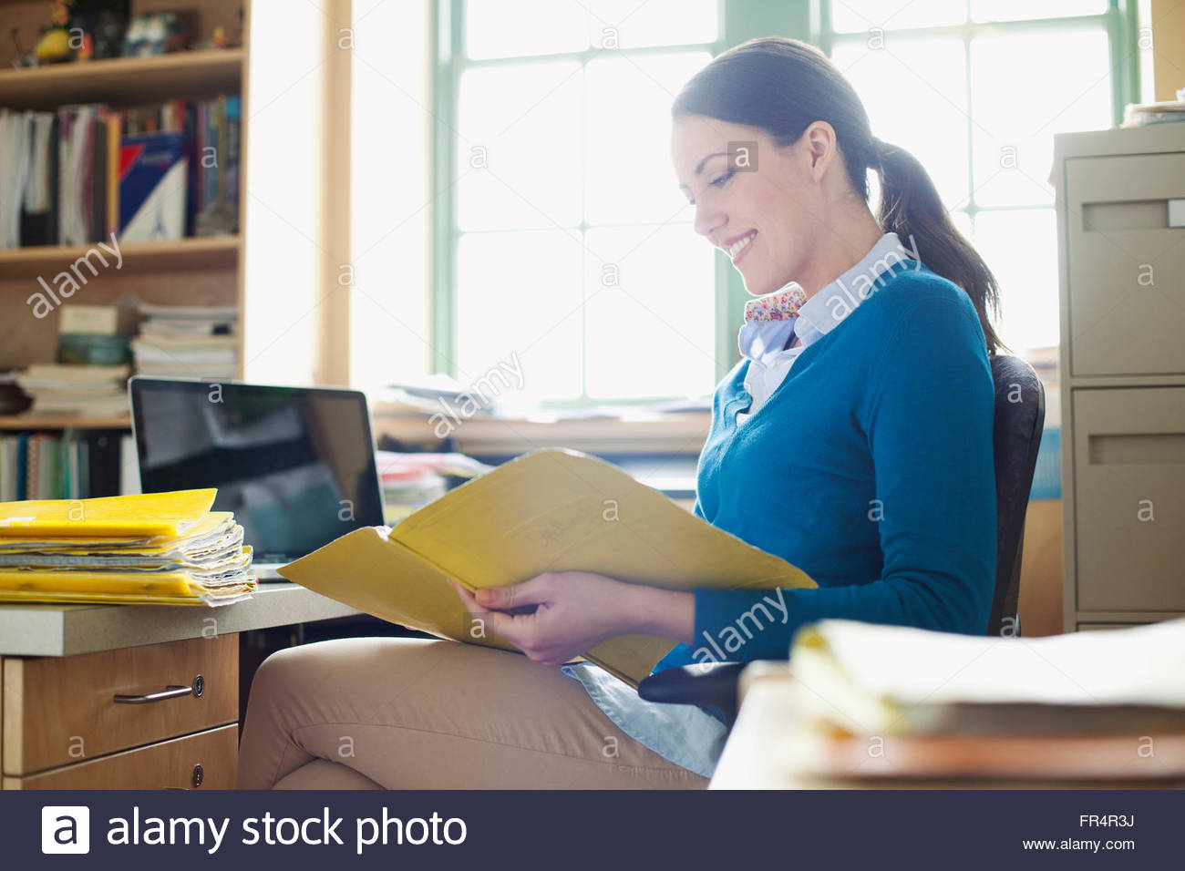 elementary school teacher reviewing papers - Stock Image