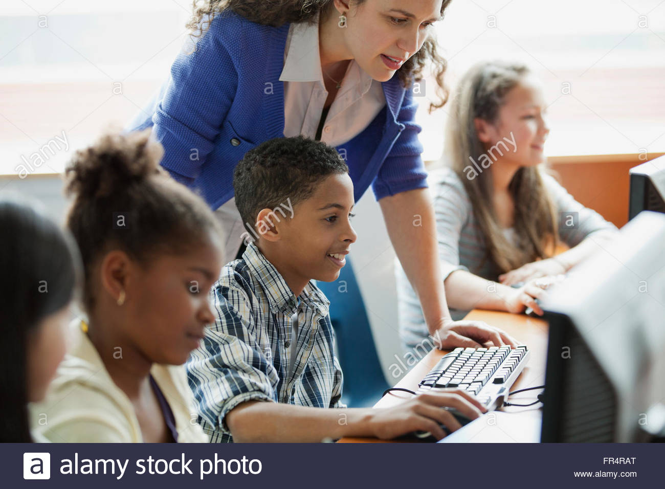 middle school students learning in computer lab - Stock Image