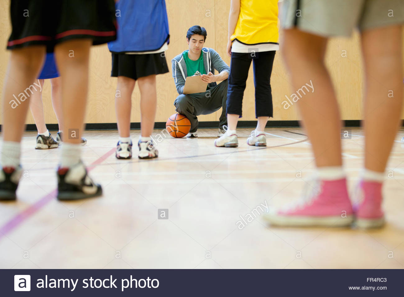 middle school students getting instruction on basketball - Stock Image